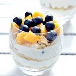 Wymieszaj jogurt z miodem, układaj na przemiennie pokrojone owoce, płatki owsiane wymieszane z otrębami i jogurt. Migdały upraż na suchej patelni teflonowej, posyp deser uprażonymi migdałami i przyozdób winogronami. Deser jest dobrze wykonać dzień prędzej wtedy płatki owsiane zmiękną.
